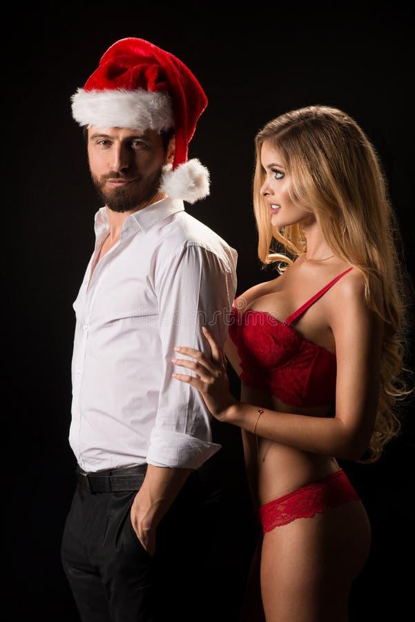 Stående av ett ungt par med jultomtenhatten arkivfoto