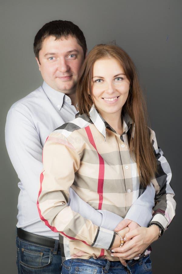 Stående av ett ungt par på grå bakgrund royaltyfri foto