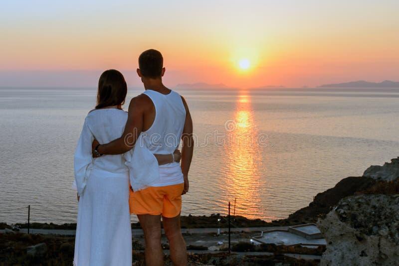 Stående av ett ungt par som kramar på solnedgången på den Santorini ön isolated rear view white Begrepp-förälskelse frihet, förhå royaltyfri bild