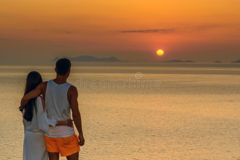 Stående av ett ungt par som kramar på solnedgången på den Santorini ön isolated rear view white Begrepp-förälskelse frihet, förhå arkivfoton
