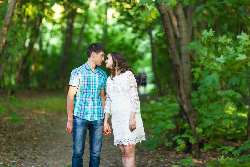 Stående av ett ungt romantiskt par som kysser sig på naturen arkivbild