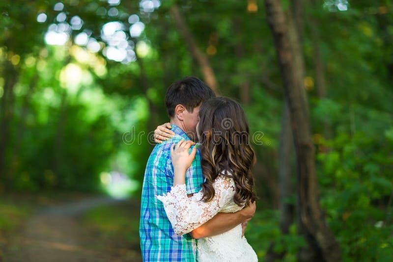 Stående av ett ungt romantiskt par som omfamnar sig på naturen royaltyfria bilder