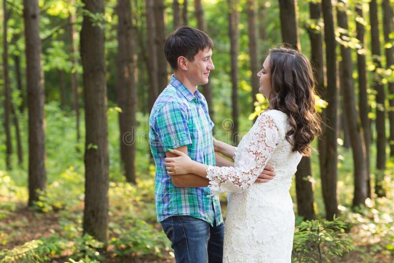Stående av ett ungt romantiskt par som omfamnar sig på naturen arkivbilder