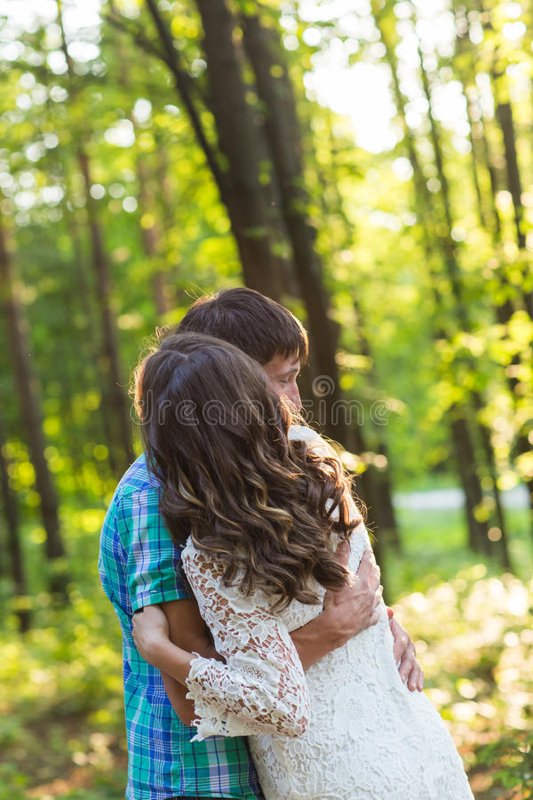Stående av ett ungt romantiskt par som omfamnar sig på naturen royaltyfri bild