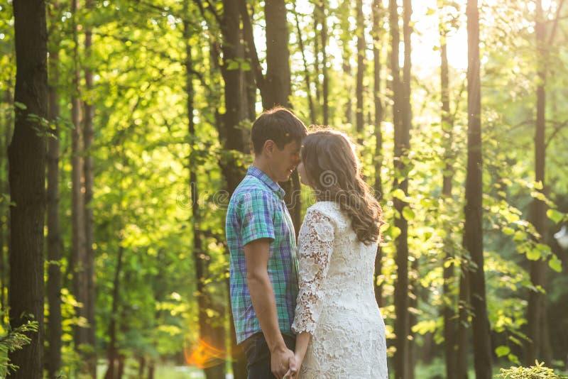 Stående av ett ungt romantiskt par som omfamnar sig på naturen royaltyfri fotografi