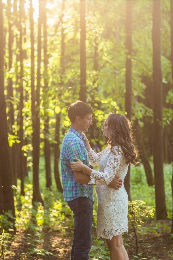Stående av ett ungt romantiskt par som omfamnar sig på naturen arkivbild