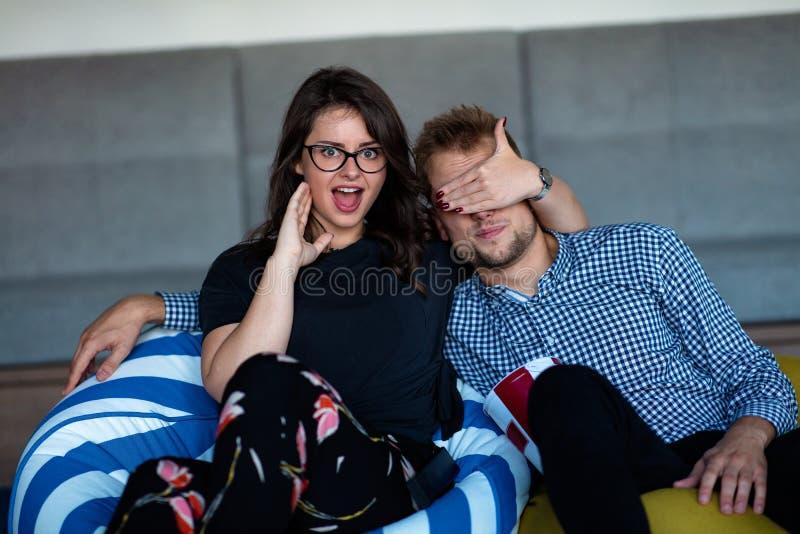 Stående av ett upphetsat ungt par som hemma kopplar av på en soffa, medan hålla ögonen på TV och äta popcorn arkivbilder