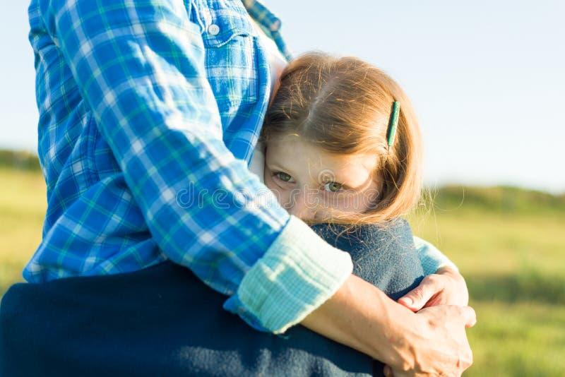 Stående av föräldern och barnet Modern kramar hennes lilla dotter Naturbakgrund, lantligt landskap, grön äng, närbild av barnet arkivfoto