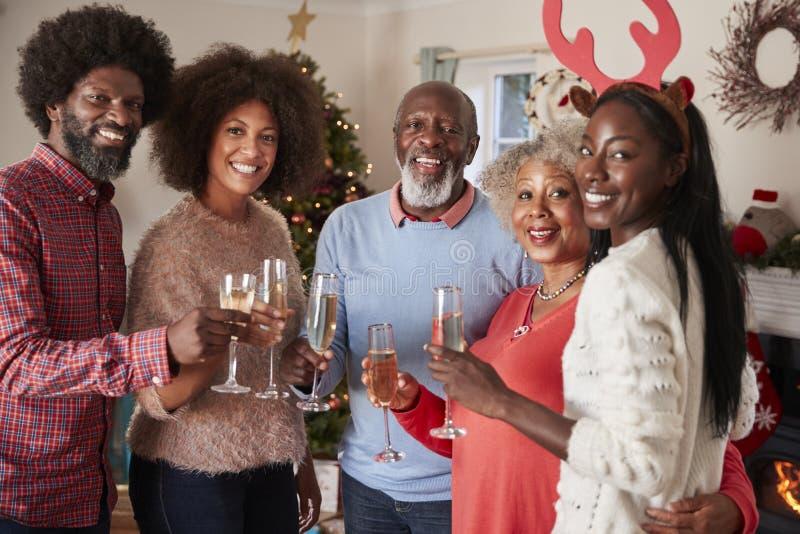Stående av föräldrar med vuxna avkommor som tillsammans gör ett rostat bröd med Champagne As They Celebrate Christmas royaltyfri foto