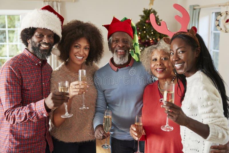 Stående av föräldrar med vuxna avkommor som tillsammans gör ett rostat bröd med Champagne As They Celebrate Christmas arkivfoton