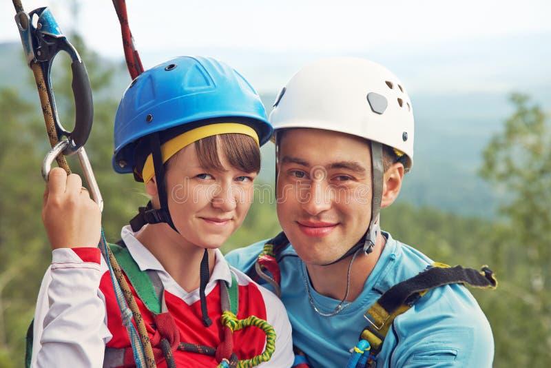 Stående av förälskade klättrare för unga par mannen och kvinnan som hänger på, vaggar på repen klättring extrem sport royaltyfri fotografi