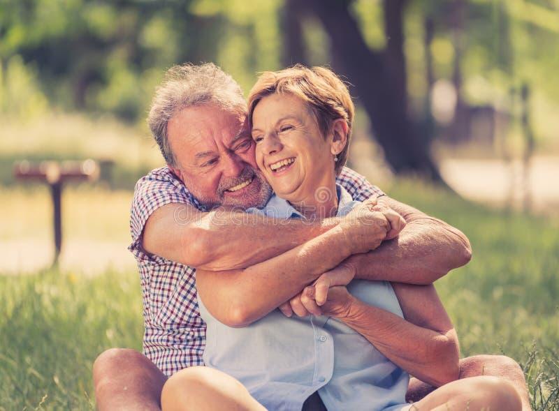 Stående av förälskat koppla av för härliga lyckliga höga par i parkera royaltyfri fotografi