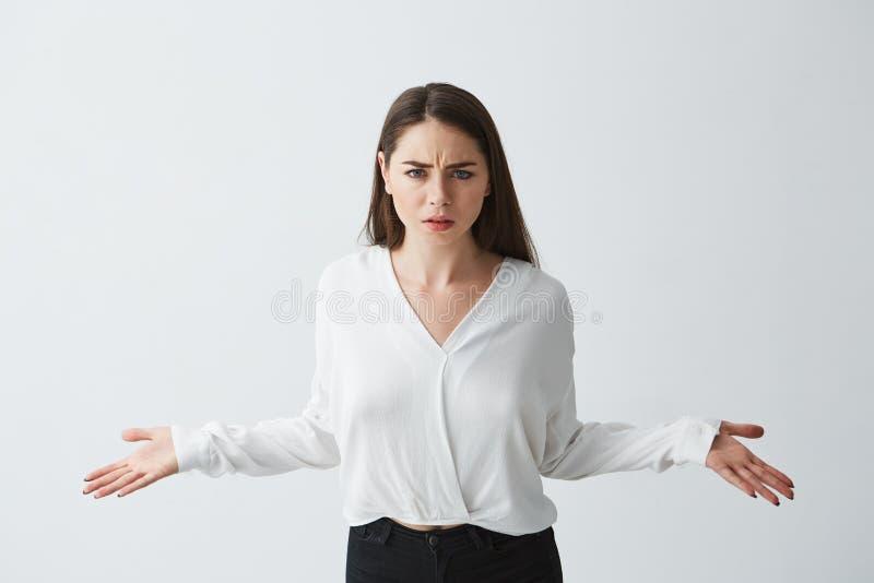 Stående av fördelande händer för missnöjd ung affärskvinna som ser ut kameran över vit bakgrund royaltyfria bilder