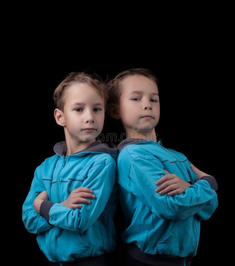 Stående av förtjusande tvilling- pojkar på svart arkivbilder