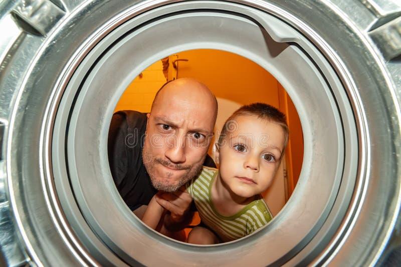 Stående av fader- och sonsikten från tvagningmaskinen inom Vad är det ting inom tvättmaskinen? royaltyfri bild