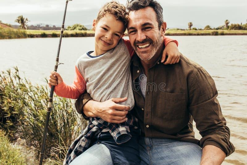 Stående av fadern och sonen som sitter bredvid en sjö arkivfoto