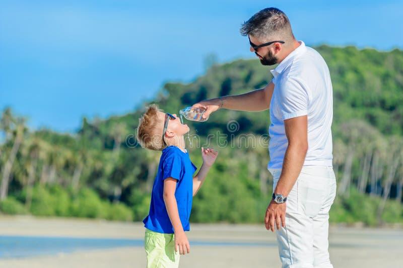 Stående av fadern som ger vatten till hans törstiga stiliga pojke på t arkivfoto