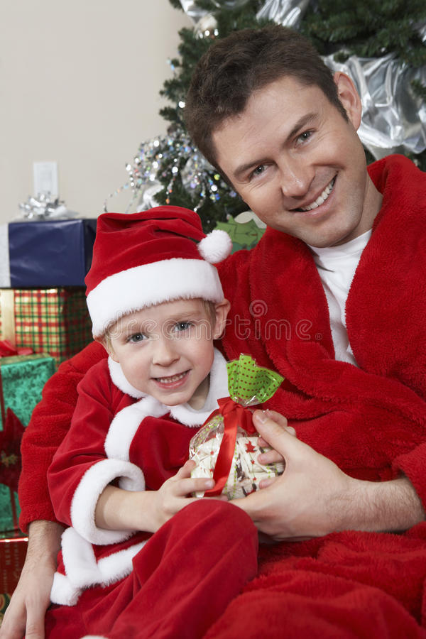 Stående av fadern And Son In Santa Claus Outfit Holding Present royaltyfria foton