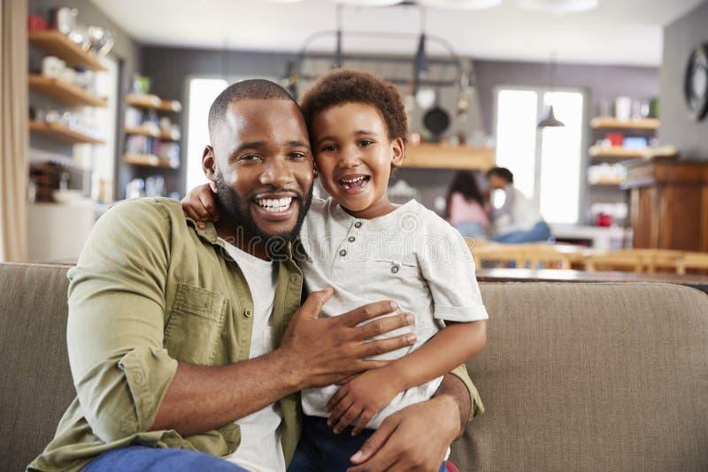 Stående av fadern And Son Sitting på Sofa In Lounge Together royaltyfri fotografi