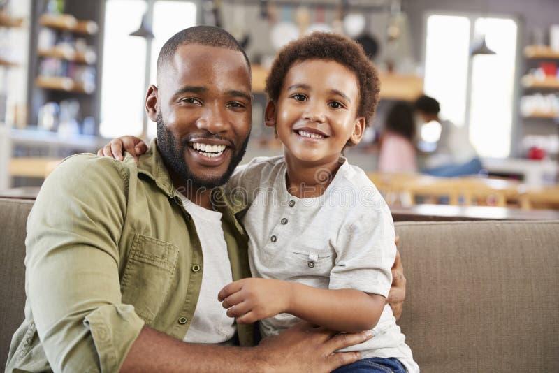 Stående av fadern And Son Sitting på Sofa In Lounge Together royaltyfria foton