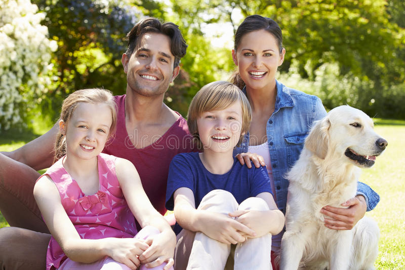 Stående av familjen med hunden som kopplar av i sommarträdgård arkivfoto