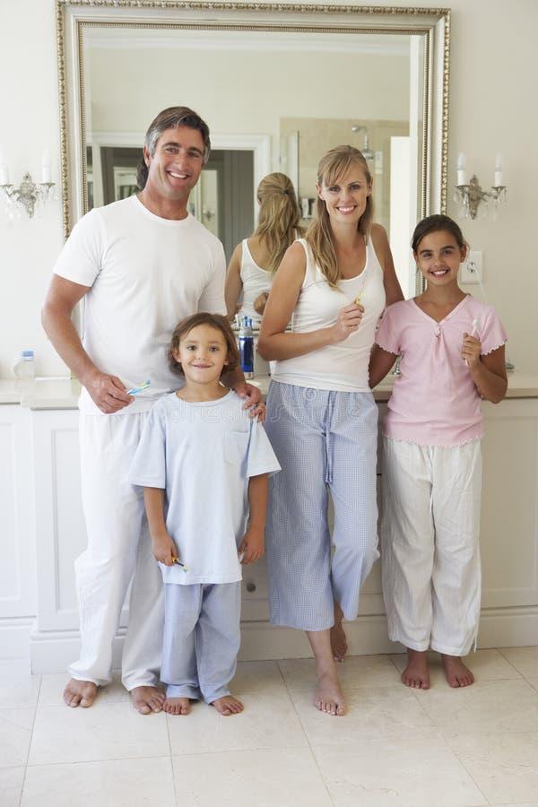 Stående av familjen omkring som borstar tänder i badrumspegel arkivbild