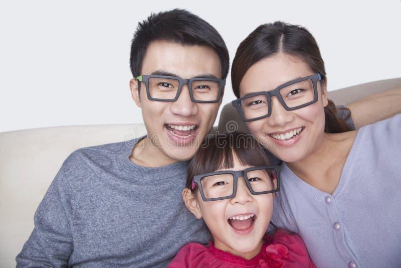 Stående av familjen som bär svarta exponeringsglas, studioskott fotografering för bildbyråer