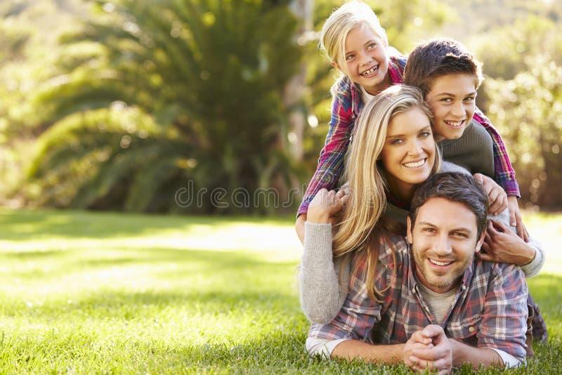 Stående av familjen som ligger på gräs i bygd royaltyfri fotografi