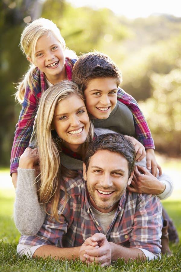 Stående av familjen som ligger på gräs i bygd royaltyfri bild