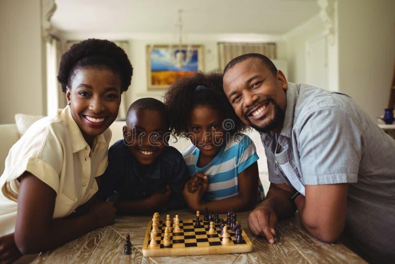 Stående av familjen som spelar schack tillsammans hemma i vardagsrummet royaltyfri foto