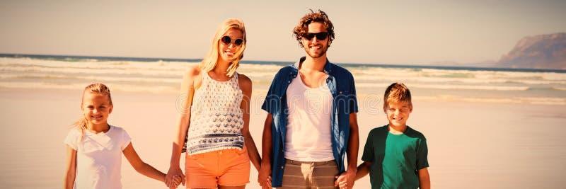 Stående av familjinnehavhänder, medan stå tillsammans på stranden royaltyfri foto