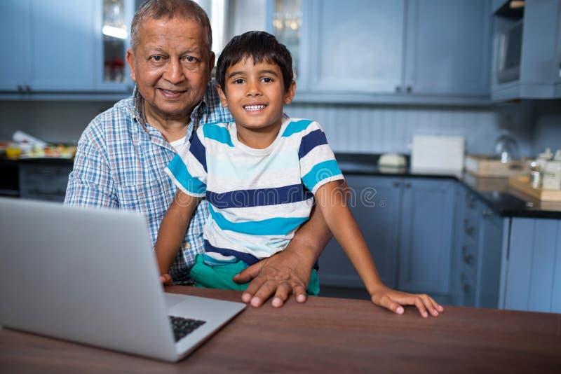 Stående av farfadern med pojken som använder bärbara datorn royaltyfri fotografi