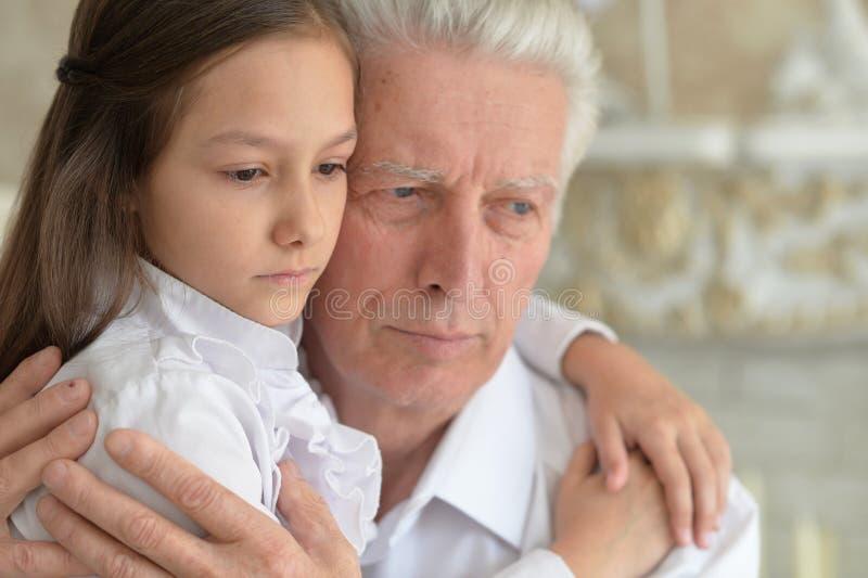 Stående av farfadern och sondottern som tänker om något arkivbild