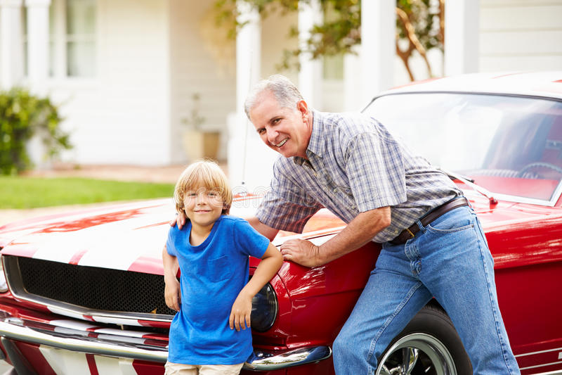 Stående av farfadern och sonsonen med den återställda bilen arkivbild