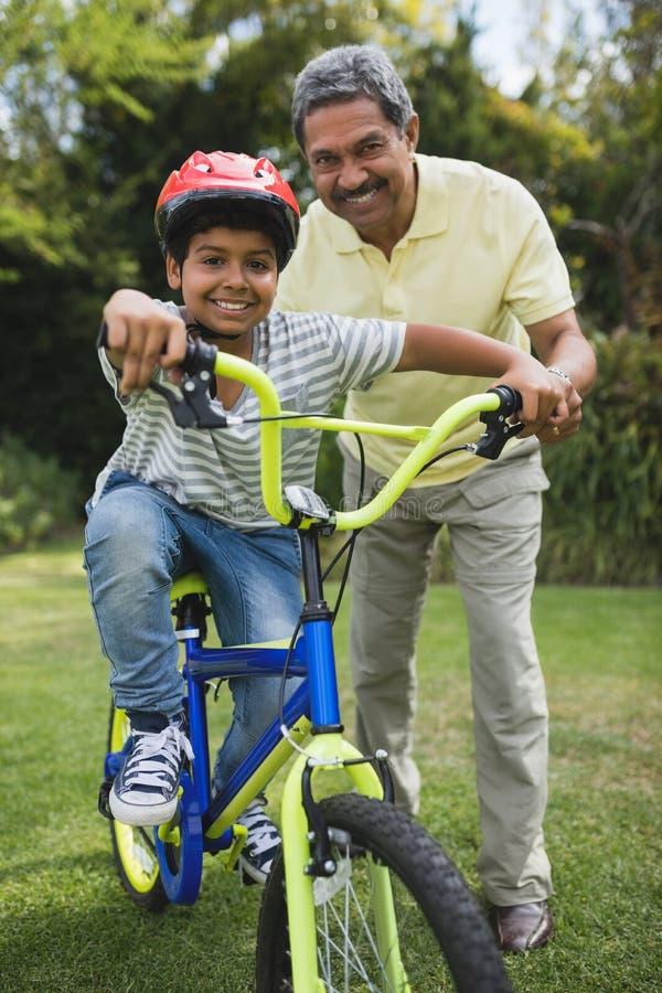 Stående av farfadern som hjälper sonsonen, medan rida cykeln arkivfoto