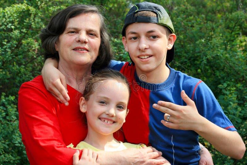Stående av farmodern som kramar två barnbarn: lite flicka och en tonårs- pojke i ett lock arkivfoton