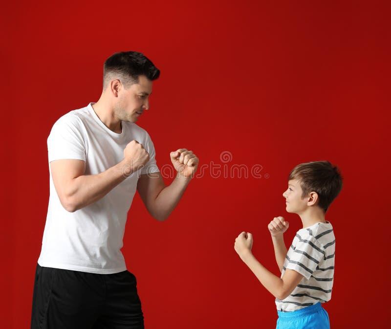 Stående av farsan och hans sonboxning arkivfoton
