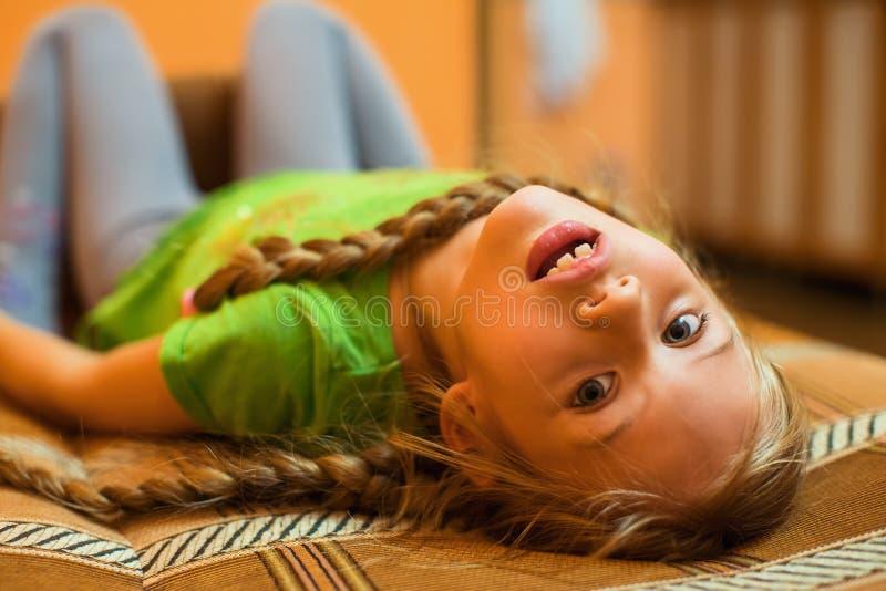 Stående av femårigt gladlynt ligga på soffan arkivfoton