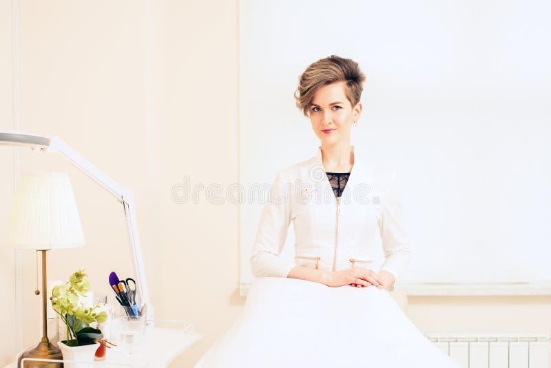 Stående av Female för härlig doktorscosmetologist en medicinsk professionell i det vita laget brunnsortcosmetologyrum royaltyfri fotografi