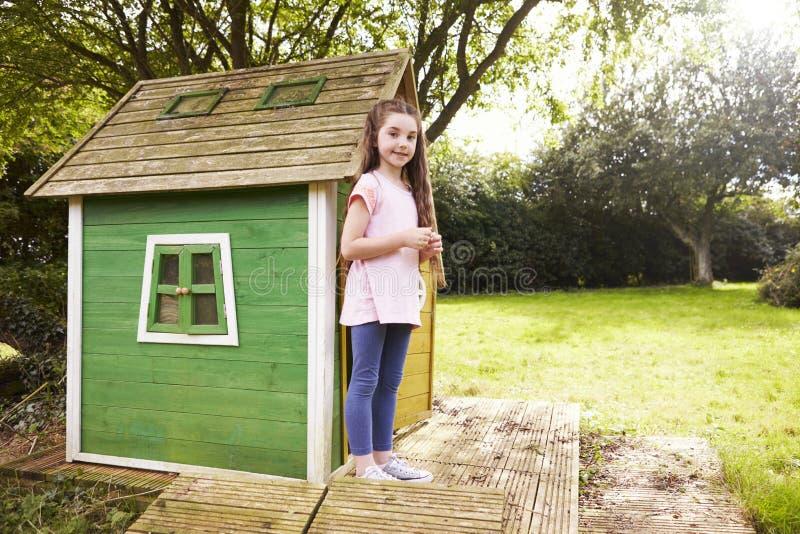 Stående av flickaanseendet i trädgård bredvid lekstuga arkivbilder