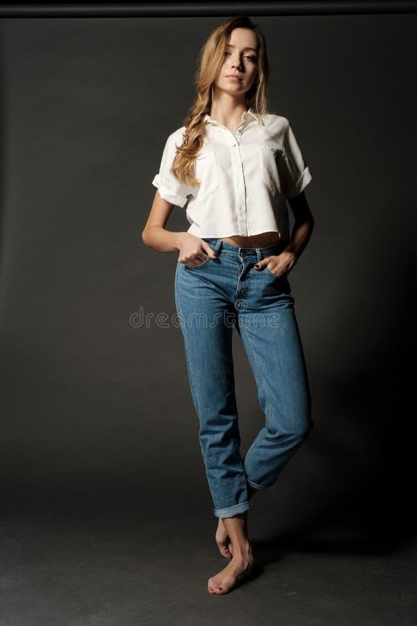 Stående av flickan av blondinen i en vit skjorta och jeans som barfota står på en mörk bakgrund, modellprov arkivfoto