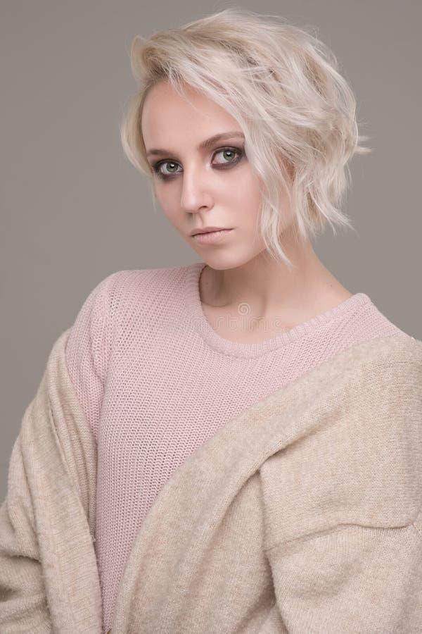 Stående av flickan av blondinen med makeup för mörkt öga och kort hår i en gräns - rosa tröja och beige överdimensionerat omslag  arkivbilder
