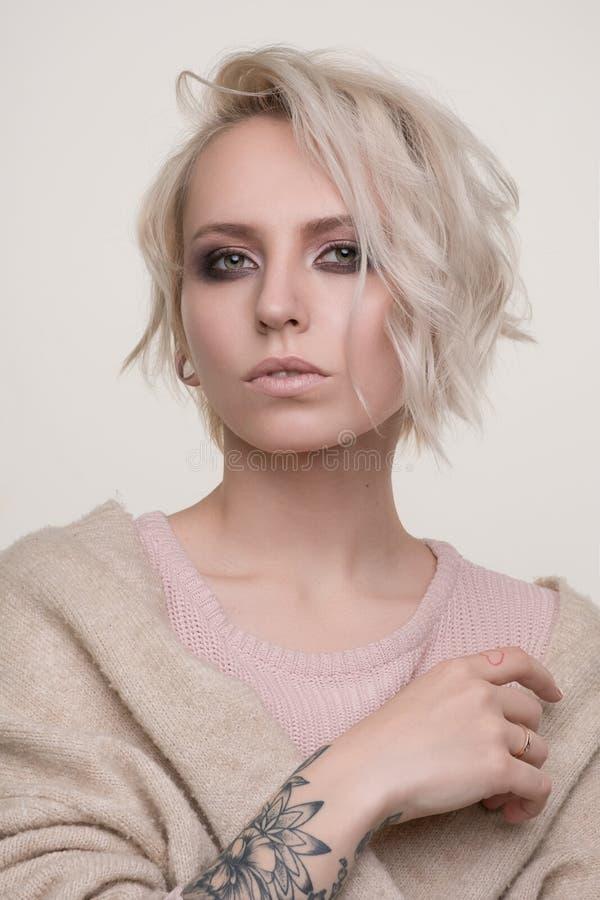 Stående av flickan av blondinen med makeup för mörkt öga och kort hår i ett ljus - rosa tröjaanseende på en ljus bakgrund som ser royaltyfria foton