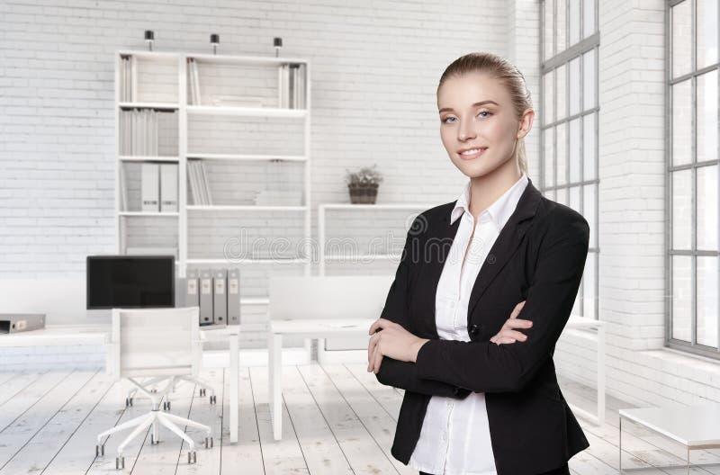 Stående av flickan i dräkt i ljust kontor arkivfoton