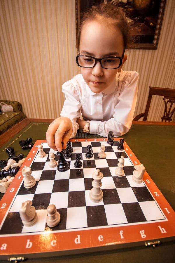Stående av flickan i glasögon som spelar schack arkivbild
