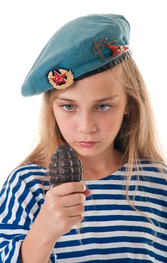 Stående av flickan i soldatbasker med en granat i hans mummel royaltyfria foton