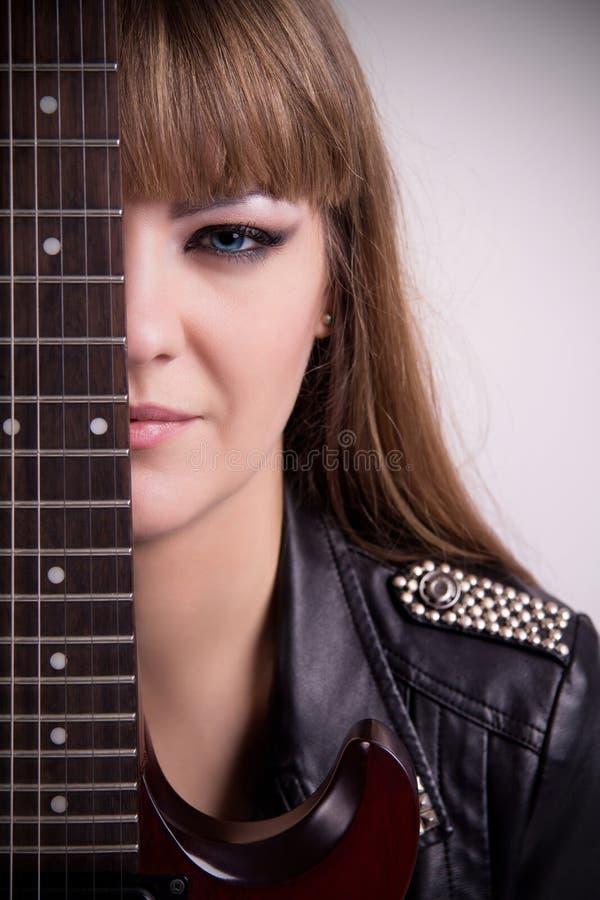 Stående av flickan med den elektriska gitarren arkivfoton