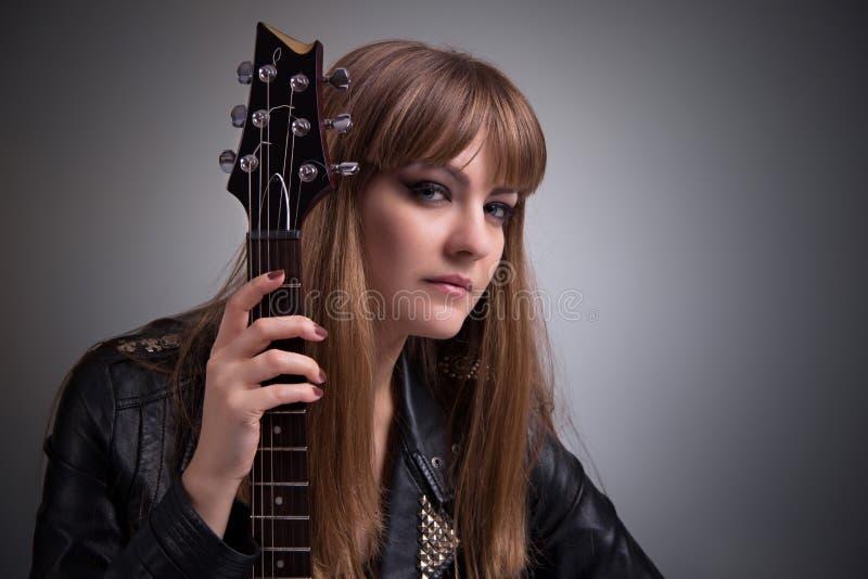 Stående av flickan med den elektriska gitarren royaltyfri bild