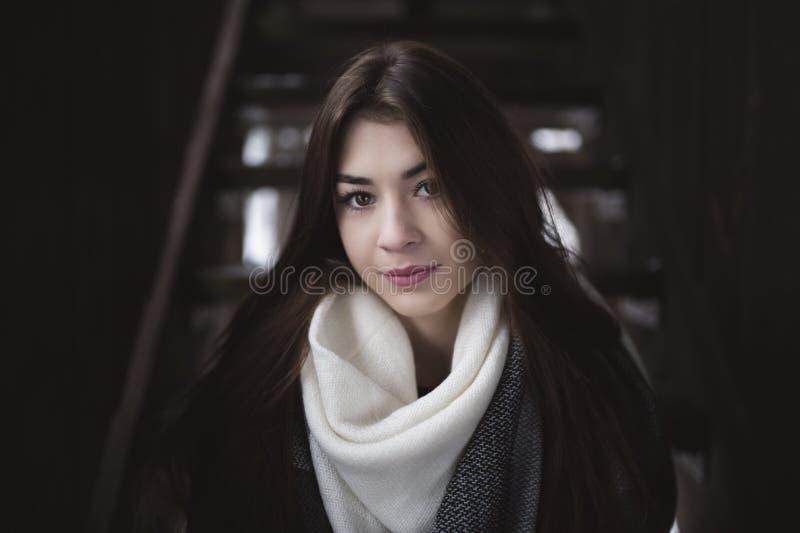 Stående av flickan med härlig blick och långt hår Inre av det övergav huset eller skjulet med mörka träväggar fotografering för bildbyråer
