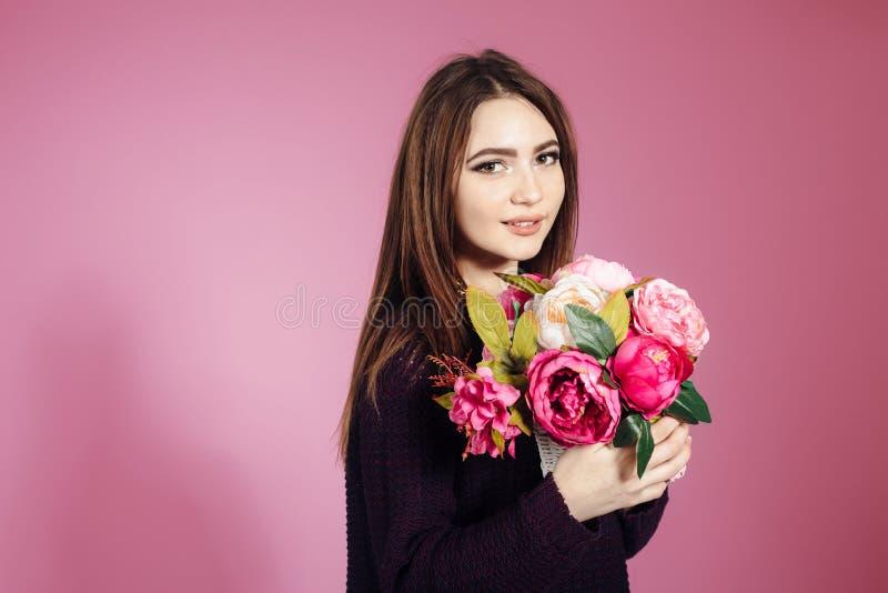 Stående av flickan med ljusa blommor på rosa bakgrund arkivbild